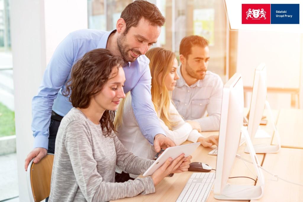 uśmiechnięci ludzie spoglądają na ekran komputera